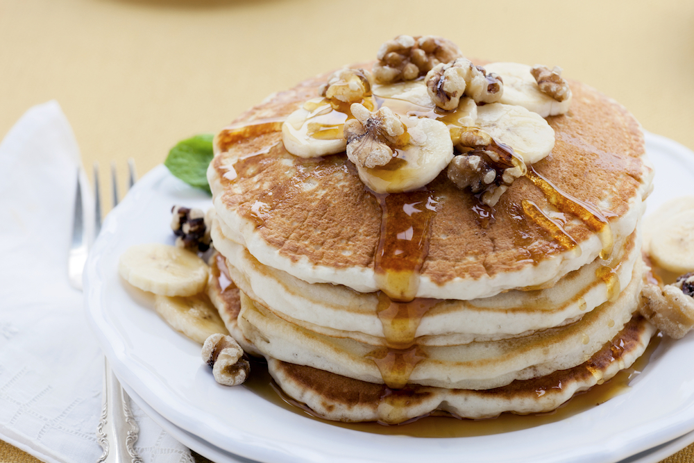 """Buttermilk pancakes topped with bananas, walnuts and maple syrup."""